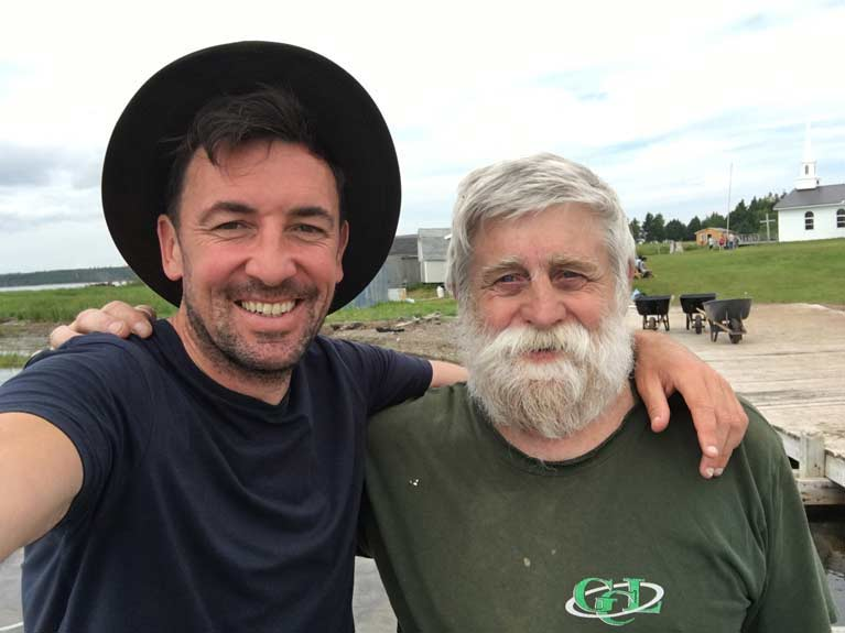 Naomhóg crewman Sean Mac an tSíthigh in cape with Nova Scotia lightkeepers grandson John Murray