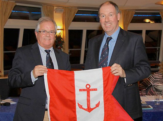 Outgoing Commodore Brian Turvey presents Berchmans Gannon with his Commodore's burgee