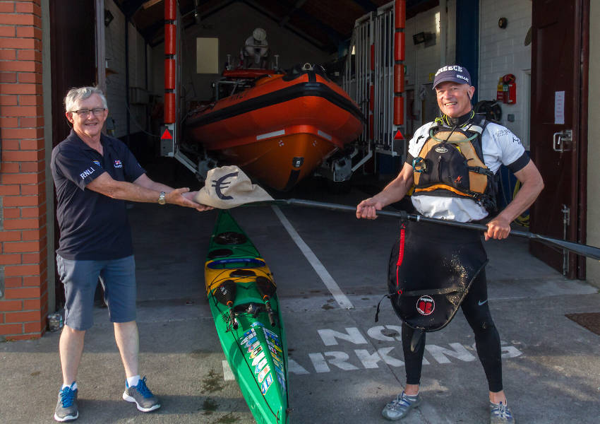 Kevin O'Sullivan using his paddle to pass the 'Bag of Swag' while maintaining social distancing (Photo: RNLI/Gerry Canning)