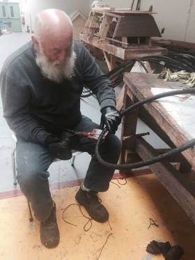 In time-honoured style, Liam O'Donoghue in the Ilen Boat Building School in Limerick parcels and serves the final pieces of Ilen's wire rigging using his traditional serving board