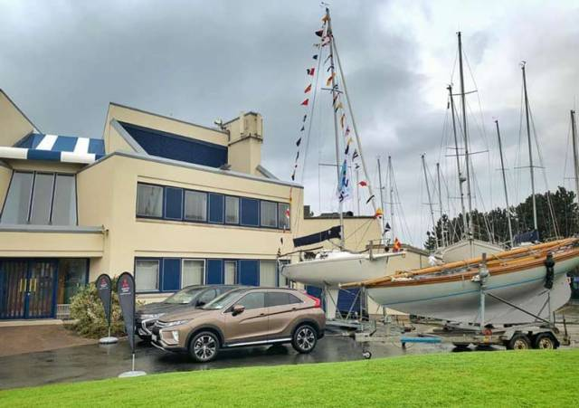 Setting the scene: Mitsubishi's popular environment-friendly Outlander PHEV on display at Howth Yacht Club last night with one of the vintage Howth 17s in company with an HYC J/80