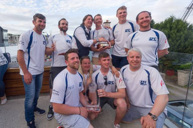 The all conquering Fools Gold crew from Waterford Harbour Sailing Club with the 2017 Sovereign's Cup. Straight wins across the series - a string of six bullets - in Class 1 IRC which was the largest division with 16 boats out of the 98-strong fleet meant Rob McConnell's result was the best score of the event. Pictured (Back row) left to right: Roy Darrer - Helm Stephen McConnell - Bow Rob McConnell - Skipper Aaron Power - Trimmer 2 Dougie Power - Mast  Graham Curran - Trimmer 1  (Front row) left to right: Stephen Ryan - Backup Trimmer Marcella Connolly - Mid-bow Greg Morrisey  - Pit Tom Fitzpatrick -Tactician. Not pictured: Brian Heneghan