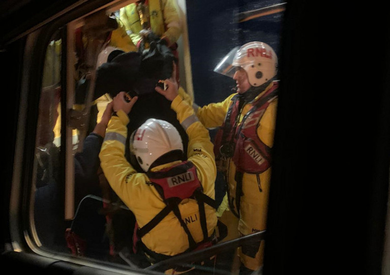 Aberdeen lifeboat crew help the casualty (in dark clothing, but wearing RNLI protective helmet and lifejacket) down the PSV's pilot ladder and aboard the all-weather lifeboat Bon Accord