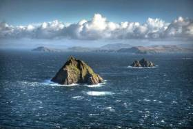 Skellig Michael, with the Little Skellig and the coast of Kerry beyond. The patch of white water in the foreground indicates the location of The Washerwoman Rock, and it has been demonstrated that it is possible to sail – indeed, to race – between it and the Skellig itself.