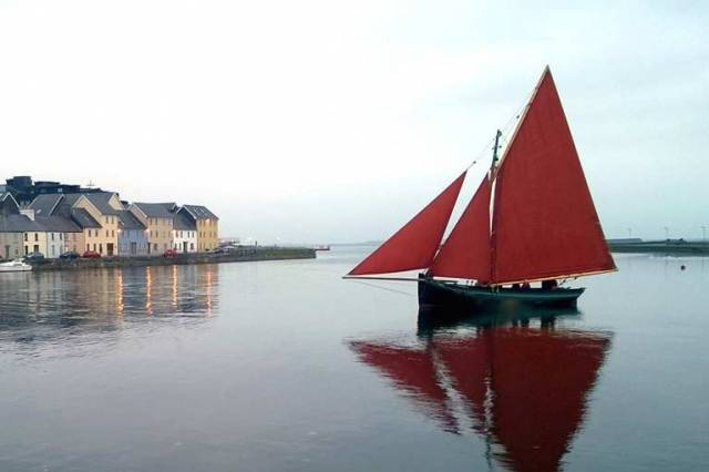 A quiet evening at the Claddagh, with a classic Galway hooker gliding along on a calm sea. But the peacefulness is going to be rudely shattered with a Viking invasion in the days ahead, just as the many traditional Galway Bay boats are gathering for their annual festival