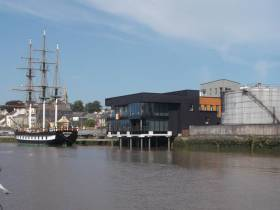 Famine replica museum ship Dunbrody alongside homeport of New Ross, Co. Wexford. New Ross Port is to be transferred to Wexford County Council within months. On the right oil tanks on the quay which are the subject of negotiations between the council and Department of Transport.