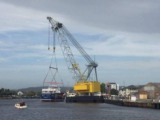 A rare example of an Irish built carferry, Spirit of Rathlin after been lowered onto the River Avoca, Arklow by the giant floating crane-barge, Lara 1