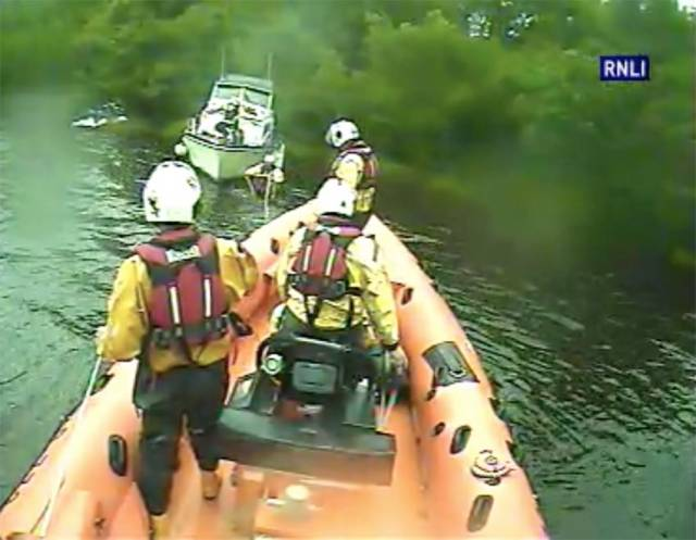 Carrybridge RNLI's volunteer crew secure a rope to tow a cruiser with motor troubles off the rocks