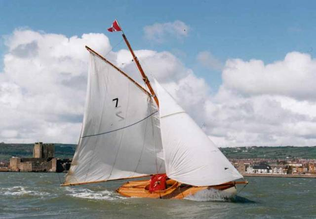 Centenary Season. Twenty years ago in April 1998, Ian Malcolm's Howth 17 Aura celebrates her Centenary by returning to her birthplace of Carrickfergus on Belfast Lough with its famous 12th Century Norman castle