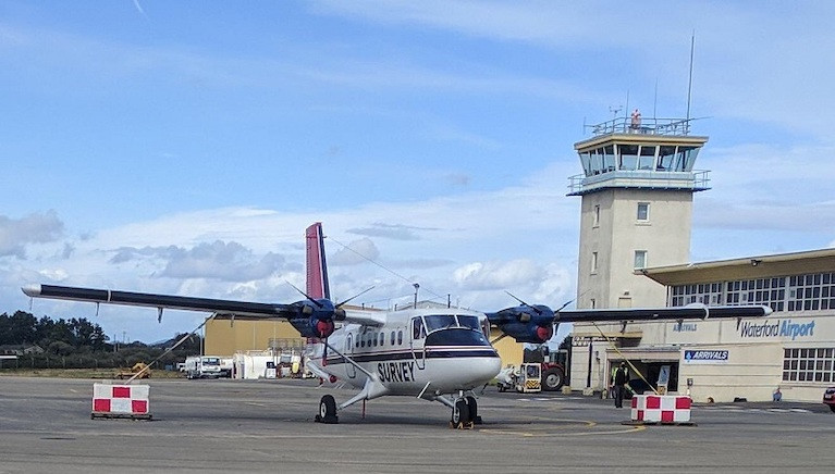 The survey aircraft is a white, twin-propeller plane (as pictured), which is easily identified by its red tail and black stripe as well as the word 'SURVEY'