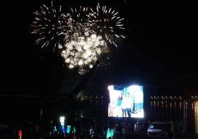 Fireworks with all the trimmings – celebration over Dun Laoghaire from the National YC while on the screen are Silver Medallist Annalise Murphy, her training partner Sara Winther, and longtime coach Rory Fitzpatrick
