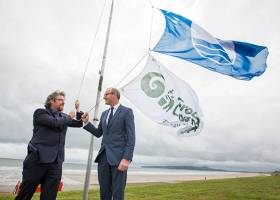 From left Michael John O'Mahony, Director, An Taisce's Education Unit; and Minister for Environment, Community and Local Government Simon Coveney TD raising the flags on Portmarnock's Velvet Strand at the announcement of  An Taisce's Blue Flag and Green Coast Awards 2016