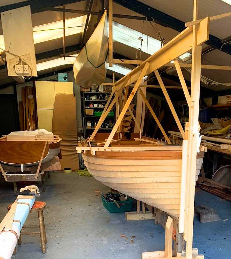 "Better than a Health Farm……the soothing setup in the McMahon shed in Athlone, with the ""new-old"" Dublin Bay Water Wag Shindilla (original built in 1932) nearing completion beside a useful little clinker-built dinghy, while a multi-purpose canoe with sailing potential is stored by suspension from the roof"