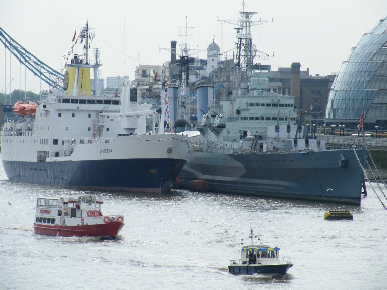 "HMS Belfast berthed in the Pool of London, named the National Historical Ships UK Flagship of 2020, for showing, along with its fellow regional flagships, ""tenacity in continuing to raise their profile throughout the Covid-19 outbreak"". In this file photo is also former St. Helena serving passenger cargoship RMS St. Helena during its historic farewell and only visit to the UK capital in 2016, before disposed following opening of an airport on the remote UK territory deep in the South Atlantic Ocean. During the mid 1990's RMS St. Helena notably visited Dublin and Cork during a cruise-charter. Afloat will have an update on this ship's sporting role!"