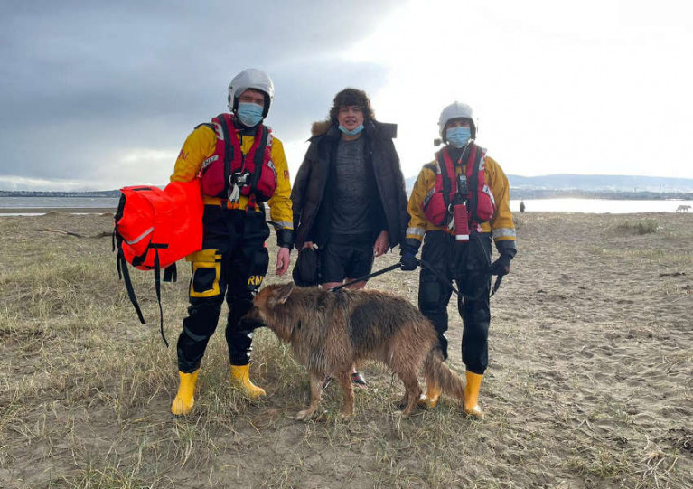 Hugo the dog and his walker with two of their rescuers