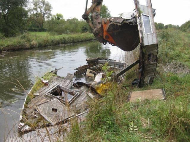 Break up of wooden sunken boat to a skip for disposal