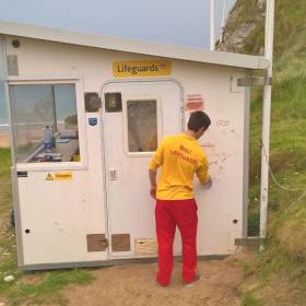A Whiterocks lifeguard cleans graffiti from the vandalised beach unit
