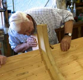 "The late Larry Duggan at his ""hobby"" of traditional boat-building. The skilled use of sawn frames to fit exactly with clinker construction was one of his specialities"