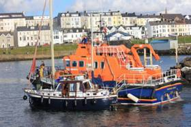 Portrush RNLI brings the cruiser under tow to Portrush harbour