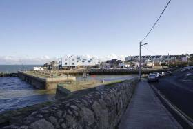 Local anger over decision to allow Bartra Capital build luxury villas and apartments at the coastal inlet at Bulloch Harbour, Dalkey in Co. Dublin and above an illustration of the proposed development.