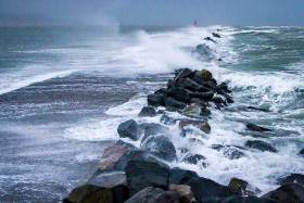 Waves break over the Great South Wall at Poolbeg, Dublin