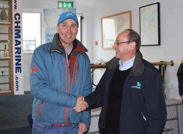 Royal St. George Laser Sailor Sean Craig receives a Craftinsure voucher from Rod Daniel
