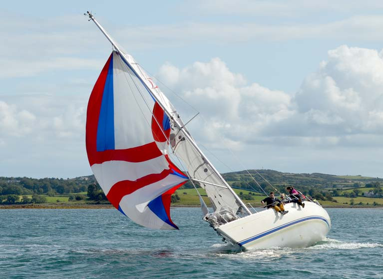 A Sigma 33 crew get to grips with a spinnaker while racing on Strangford Lough in 2019