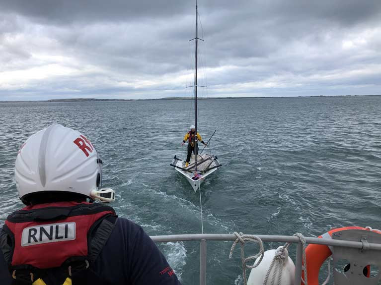 The RS skiff dinghy under tow and RNLI crewman on board