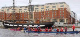 Dragon boats racing with the back drop of the Tall Ship Jeanie Johnston on the River Liffey