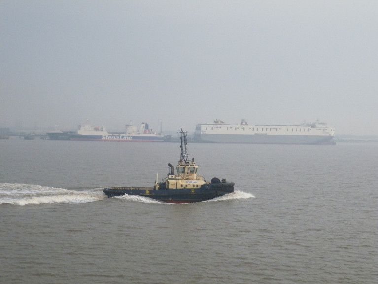 Brexit 'Freeports': Logistics UK welcomes the move to offer 'an ambitious customs model, measures to speed up planning processes, and a commitment to geographic flexibility and opportunities for all transport modes'. Above AFLOAT's photo of a hazy Humber Estuary (Killingholme) on the North Sea. On the right Delphine which in 2018 joined sister Celine dubbed the 'Brexit-Buster' on Ireland-mainland Europe services of Dublin-Belgium/Netherlands. On the left another ro-ro freight-ferry Stena Scotia currently operates on the Irish Sea between Belfast and Heysham, England. In the foreground heading upriver the 70 bollard pull tonnes tug Svitzer Laura.