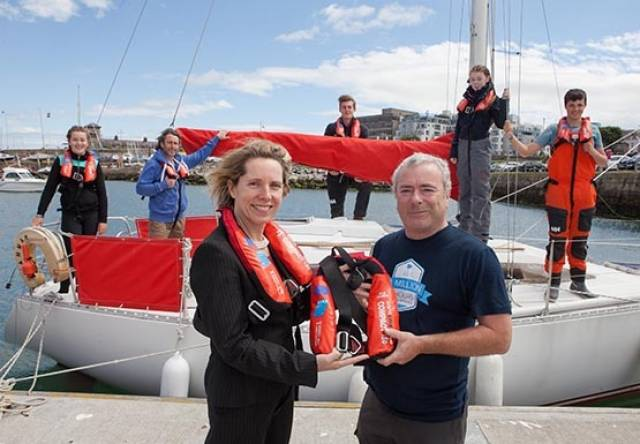 Bord Iascaigh Mhara (BIM) CEO Tara McCarthy presents one of the new compact lifejackets with  integrated personal locator beacon to Kyron O'Gorman, Principle of Irish Youth Sailing Club Dun  Laoghaire. Pictured in the background are Hannah Quigley (13) from Blackrock; Eugeen McCann  (Skipper), Kieran Hall (17) from Glenageary; Sorcha Duffy (13) from Deansgrange and Alan Roche  (15) from Dundrum