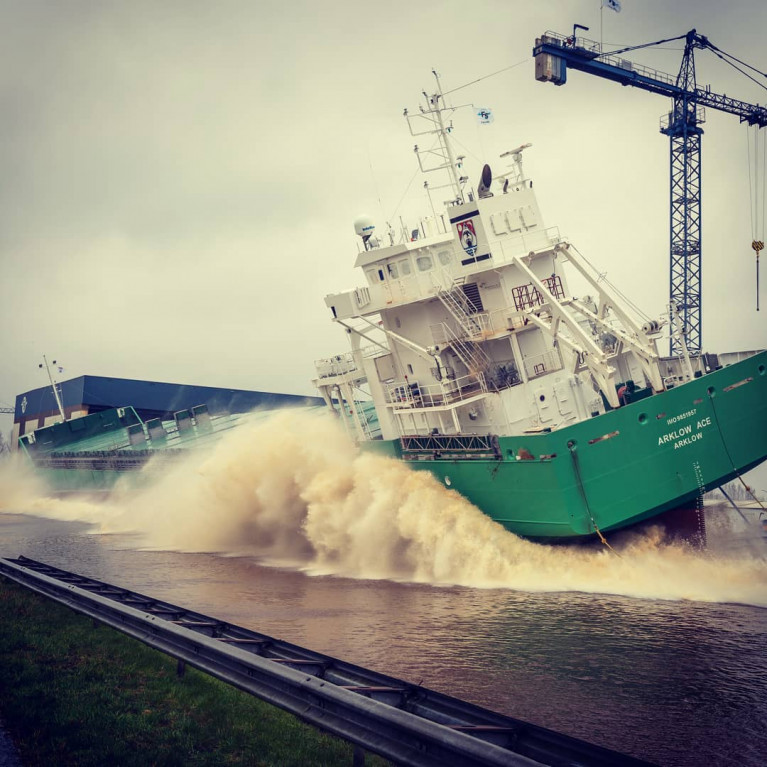 File photo of the latest newbuild Arklow Ace (in centre, when still in construction) is the third of six A-series ships launched from a shipyard in the Netherlands. AFLOAT adds note the barge delivering a load of hatch covers and gantry to be lifted on board the newbuild.