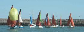 Tears in Heaven shows the fleet how to fly her spinnaker in the light winds of Dun Laoghaire Harbour
