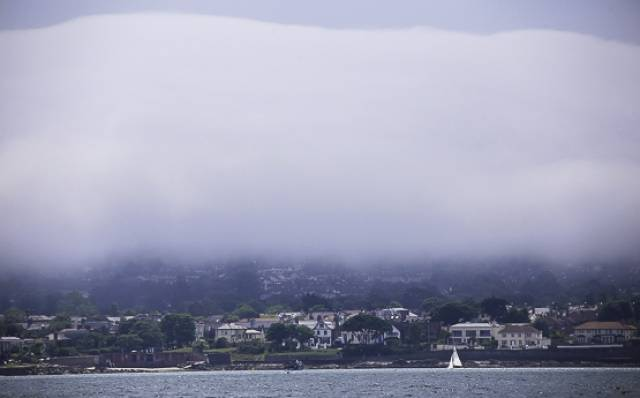A lone Fireball dinghy sails on Dublin Bay with a backdrop of heavy mist on Killiney Hill on Saturday