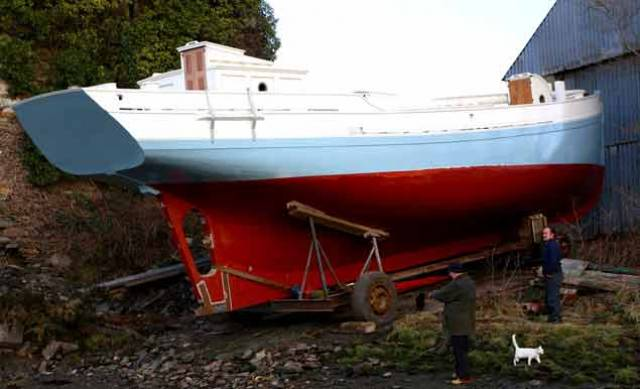 Waiting for the tide. Even the normally snooty boatyard cat shows a measure of approval for the restored Ilen as everyone waits for the tide