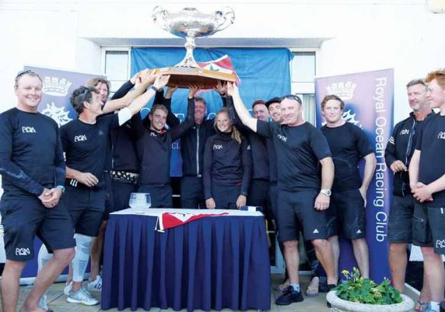 Justin Slattery (fourth from right) lifts the One Ton Cup in Cowes