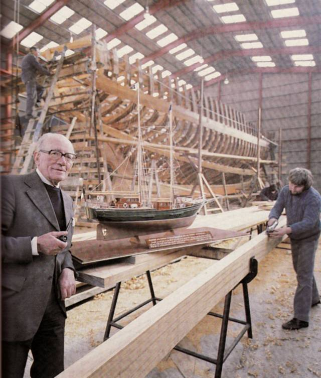 Jack Tyrrell in 1979 the great shed in Arklow in which Asgard II was built. He is seen foreground with the ship's model which he used to promote the ideal at boat shows and to government ministers, while in the background Asgard II finally takes shape