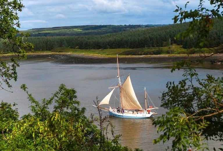 Ilen departs Foynes, on passage for Kilronan in the Aran Islands. Conor O'Brien – Ilen's designer in 1926 – ensured that all his major voyages essentially started from Foynes, his home port where he lived on Foynes Island