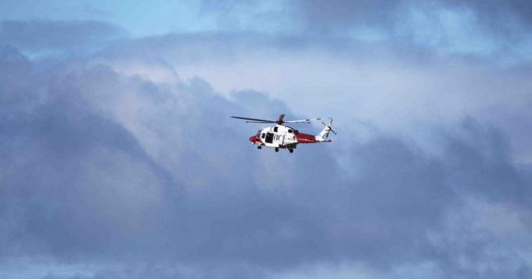 The body of a man was found on the shore near Ynys Y Fydlyn in Anglesey on Wednesday. Above a UK Coastguard helicopter involved in the search off north Wales.