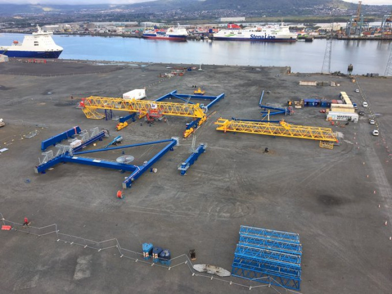 Funding for phycial posts in Northern Ports. AFLOAT adds updates on Belfast Harbour (as above) freight and passenger ferries of Stena Line berthed at the VT2 terminal and partially in the photo is ro-ro freight ferry Stena Forecaster (which Afloat reported in April) was temporarily withdrawn from Belfast-Birkenhead (Liverpool) route due to impact of Covid19. The freightship had since returned to service but as of this morning's Afloat tracked inbound sailing, noting subsequent services on the Irish Sea route have been cancelled by this ship until 1 June. Also in the foreground is a ship to shore (STS) container crane which was transported by sea from Cork Harbour (reported in March) which have since been erected. The STS crane was moved to VT3 to increase efficiency of handling essential goods for Northern Ireland.