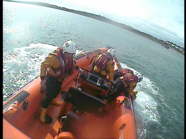 Volunteers on the inshore lifeboat Louis Simson bring the male swimmer back to shore for treatment