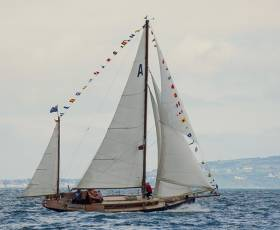 "The jib topsail blossoms to drive Dickie Gomes' Ainmara on her way as she sails fast to collect the ""Best in Show"" award at the RUYC's 150th Anniversary Sail-past, fifty years after she took part in the same Club's Centenary Regatta in 1966 with the same crew on board"