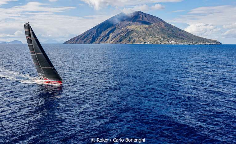 The Rolex Middle Sea Race mono-hull leader, I Love Poland, a Volvo 70, comes past Stromboli at a safe distance not to avoid volcanic eruptions, but to stay out of the notorious inshore calms