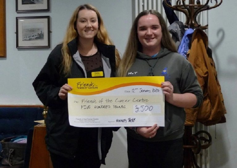 CAYC junior vice captain Hannah Todd presenting Amy from Friends of the Cancer Centre with a cheque for £500