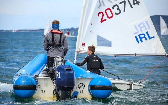 Radial sailor Johnny Durcan from Royal Cork alongside his coach–boat before a race at this summer's Laser Radial Youth Worlds in Dun Laoghaire. Durcan is among the talented Junior All Ireland Championships line–up in Schull, West Cork tomorrow