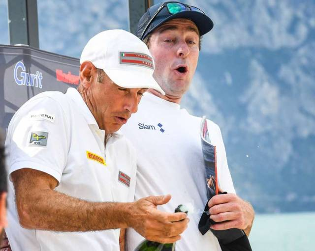 Third overall David Kenefick (right) reacts to the pop of the Champagne cork on the podium at Lake Garda Foiling Week