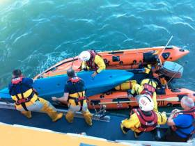 RNLI volunteers assist one of the three kayakers who attempted to aid the rescue of an injured teenager in Courtown Harbour, as featured on BBC Two's Saving Lives at Sea this Thursday 23 August