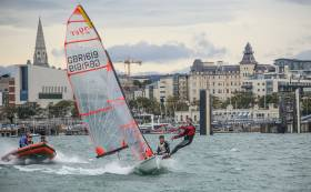 A 29er junior skiff dinghy flies past the Royal St. George Yacht Club during try–out sessions in Dun Laoghaire Harbour