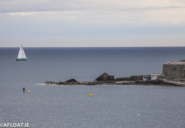 A yacht makes its way past Sandycove on Dublin Bay watched by a Stand Up Paddleboarder at the Forty Foot