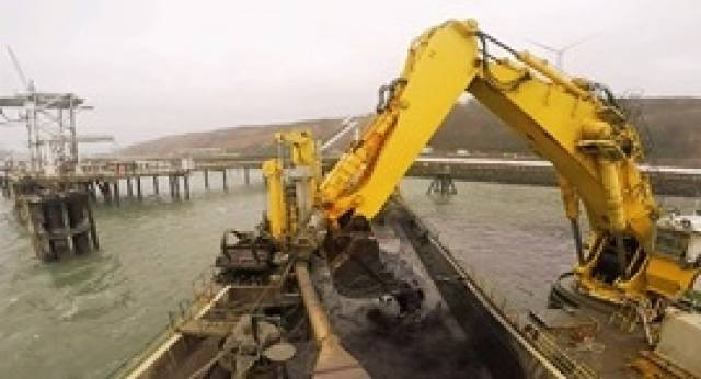 The giant bucket of the dredging vessel Mimar Sinan clears sediment from a jetty in the Port of Milford Haven